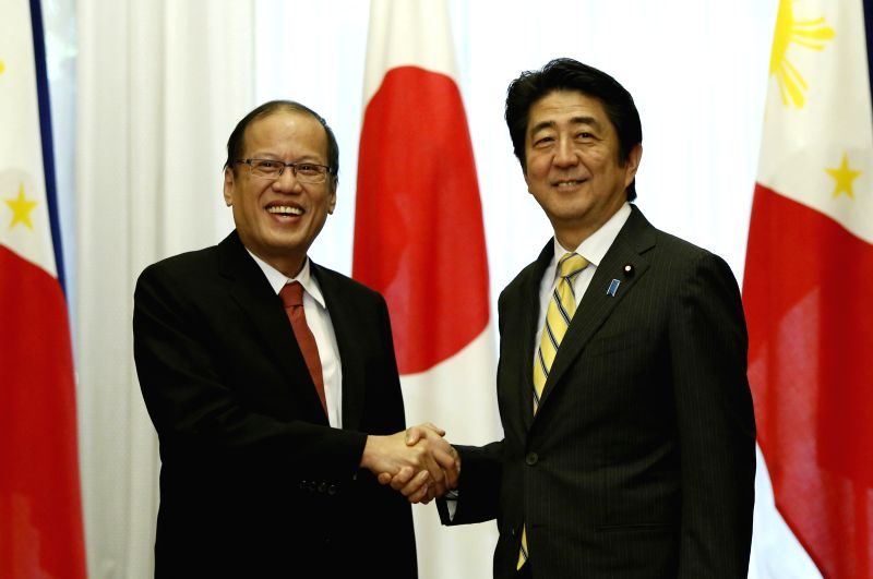 Japan's Prime Minister Shinzo Abe (R) shakes hands with visiting Philippines President Benigno Aquino III at the prime minister's official residence in Tokyo, capital