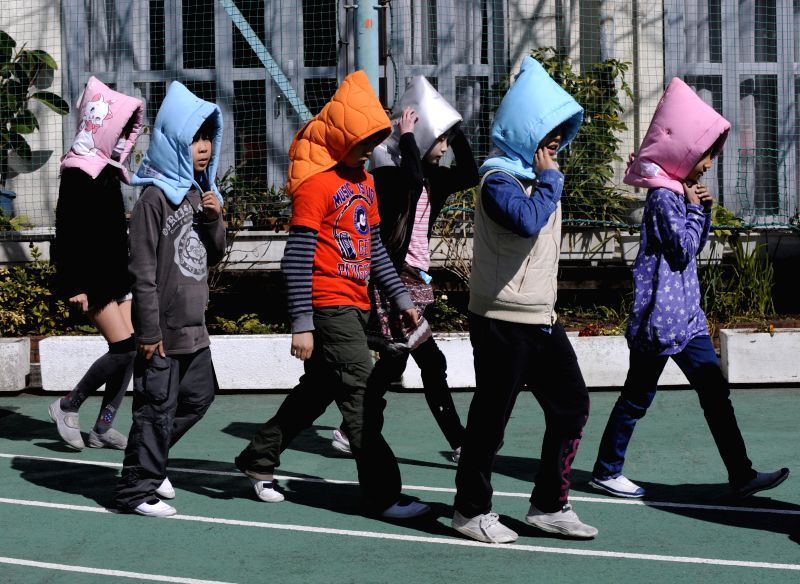 Elementary school children in disaster prevention hoods take part in a disaster drill in Tokyo, Japan, March 11, 2015.