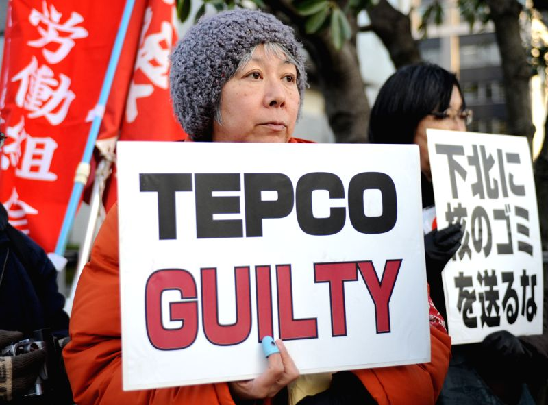 People hold placards to protest against Tokyo Electric Power Company (TEPCO), owner and operator of the crisis-hit Fukushima Daiichi nuclear power plant, in front of ...