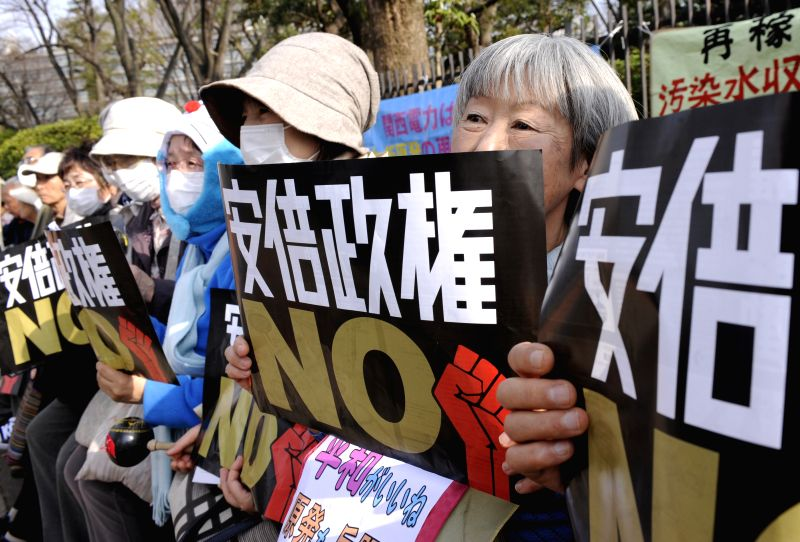 People attend a demonstration against Japanese Prime Minister Shinzo Abe in Tokyo, Japan, March 22, 2015. - Shinzo Abe