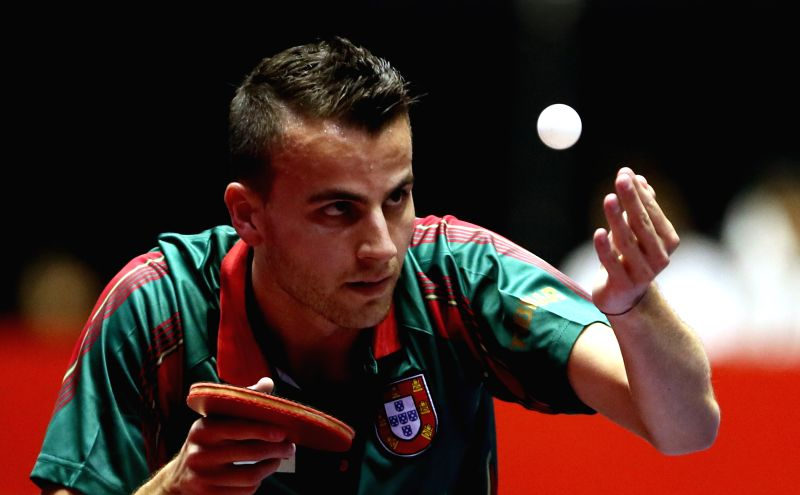 Tiago Apolonia of Portugal serves the ball against Mizutani Jun of Japan during their men's teams match at the Zen Noh 2014 World Table Tennis Championships in Tokyo, ..
