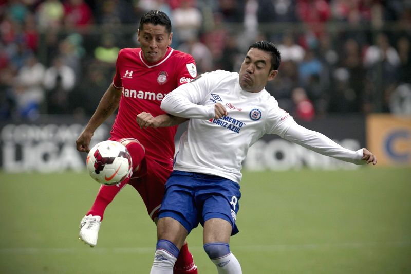 Toluca's Carlos Esquivel (L) vies for the ball with Marco Fabian of Cruz Azul during the second leg match of the CONCACAF Champions League Final at Nemesio Diez ...