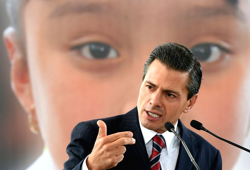 """Image provided by Mexico's Presidency shows Mexican President Enrique Pena Nieto takes part in a ceremony for the opening of the elementary school """"Isidro ..."""