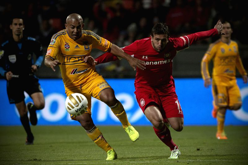 Jeronimo Amione (R) of Toluca vies for the ball with Raul Arevalo of Tigres during their semi-finals match of Opening Tournament of the MX League, at Nemesio Diez Stadium, in Toluca, Mexico ..