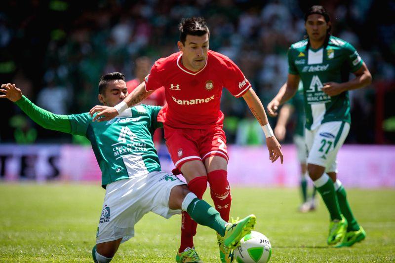 Toluca's Edgar Benitez (C) vies for the ball with Juan Jose Vazquez (L) of Leon during their second leg semifinal match of the Liga MX Closing Tournament at Nemesio ..