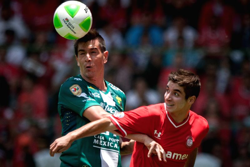 Toluca's Isaac Brizuela (R) vies for the ball with Juan Ignacio Gonzalez of Leon during their second leg semifinal match of the Liga MX Closing Tournament at Nemesio .