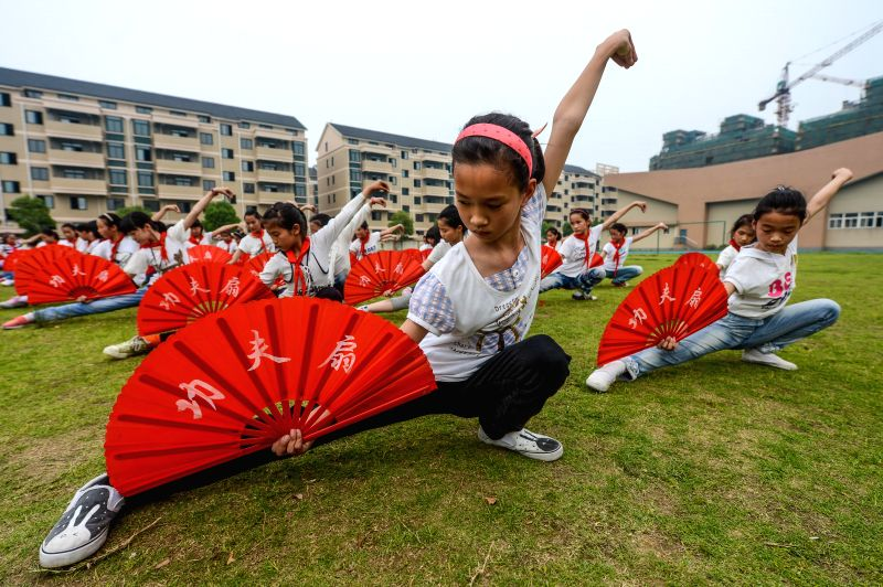 Over 300 students perform Kongfu with fans at Chongde Primary School in Chongfu Town of Tongxiang City, east China's Zhejiang Province, May 16, 2014. The school ...