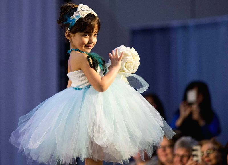A girl presents a young bridesmaid dress during the fashion show of the 2015 Toronto's Bridal Show at the Exhibition Place in Toronto, Canada, April 11, 2015. ...
