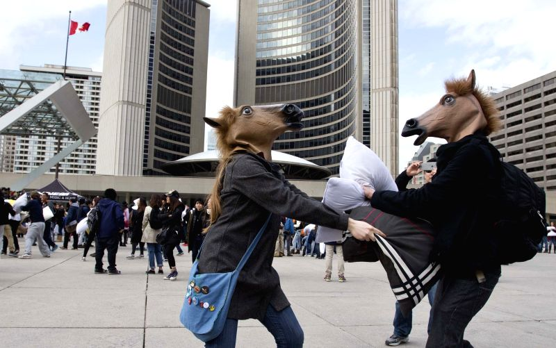 People wearing horse head masks take part in the 2015 pillow fight event at the Nathan Phillips Square in Toronto, Canada, April 4, 2015. The 2015 International ...