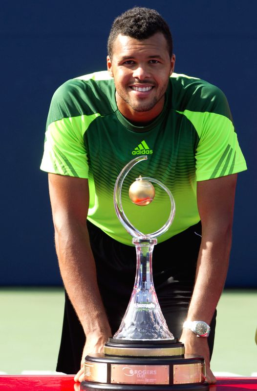 Jo-Wilfried Tsonga of France poses for photos with his trophy after the final of men's singles against Roger Federer of Switzerland at the 2014 Rogers Cup in ...