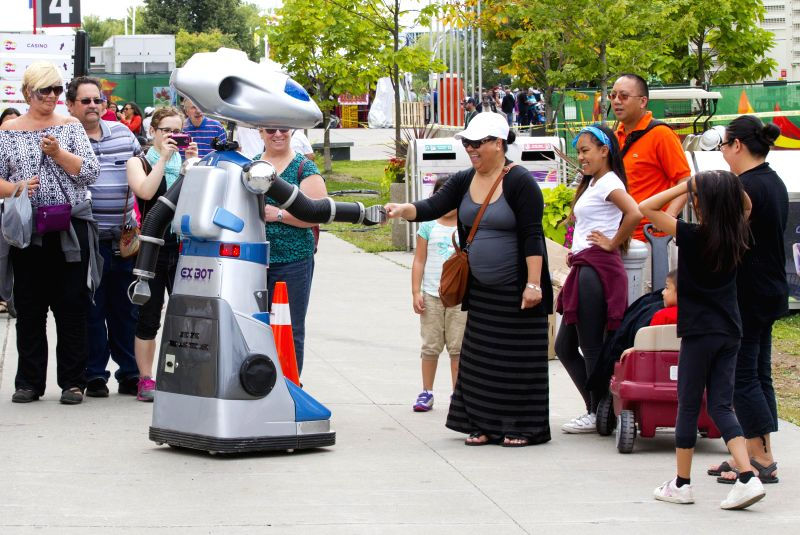 A robot shakes hands with a woman during the 2014 Canadian National Exhibition in Toronto, Canada, Aug. 15, 2014. Kicked off on Friday, the 18-day event is expected
