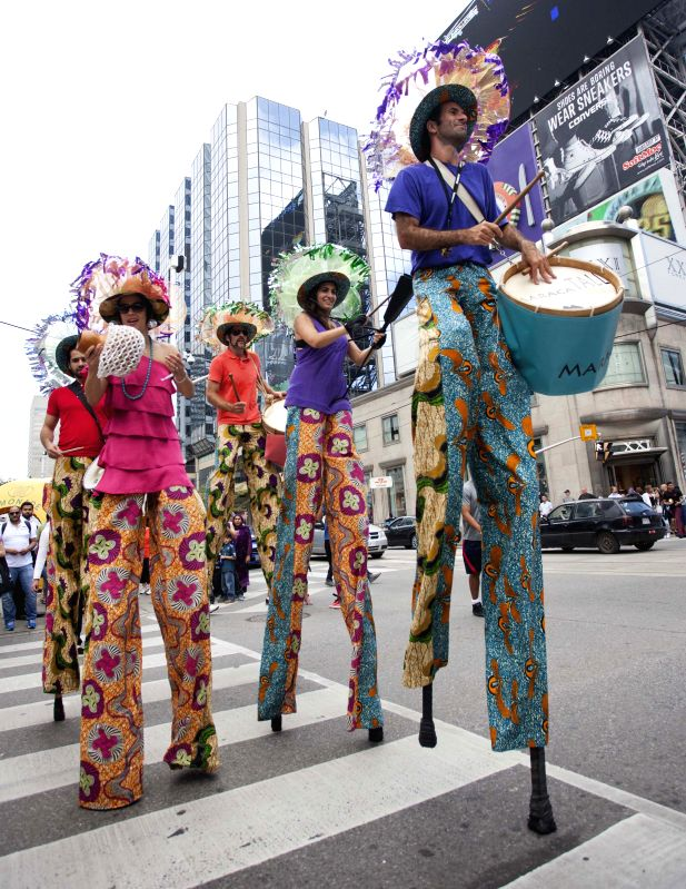 A band walks on stilts to perform during the 15th BuskerFest in Toronto, Canada, Aug. 21, 2014. Kicked off on Thursday, the four-day street fesitival with more than