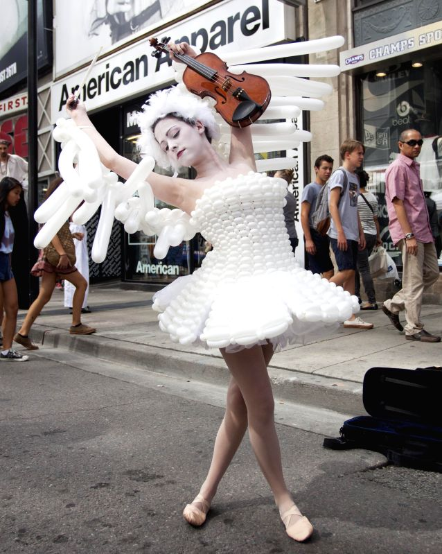 A woman dressed in white ballons performs during the 15th BuskerFest in Toronto, Canada, Aug. 21, 2014. Kicked off on Thursday, the four-day street fesitival with ..