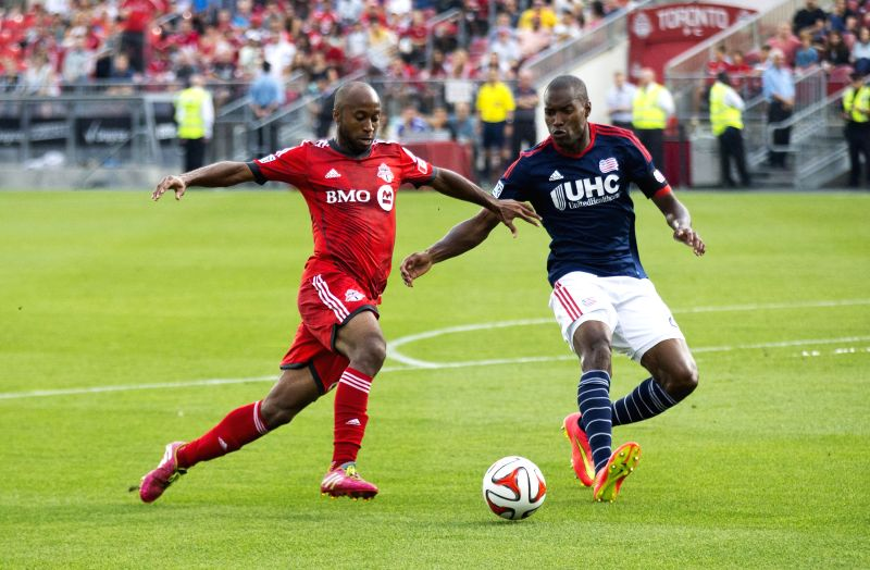 Jose Goncalves (R) of New England Revolution vies with Collen Warner of Toronto FC during their 2014 Major League Soccer (MLS) match in Toronto, Canada, Aug. 30, ...