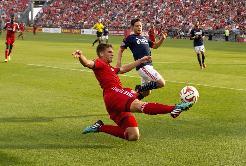 Nick Hagglund (front) of Toronto FC passes the ball during the 2014 Major League Soccer (MLS) match against New England Revolution in Toronto, Canada, Aug. 30, ...