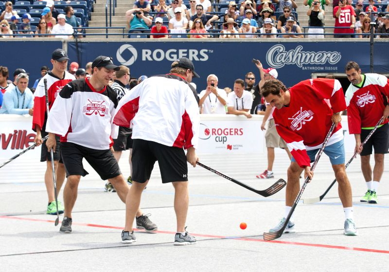 Roger Federer (2nd R) of Switzerland battles for the ball during the Ball Hockey Challenge game at the 2014 Rogers Cup in Toronto, Canada, Aug. 3, 2014. (Xinhua/Zou .