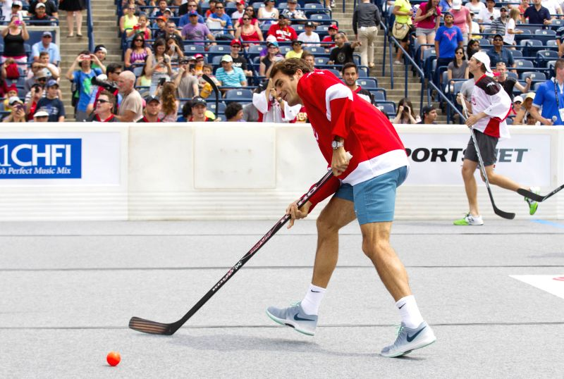Roger Federer (L) of Switzerland takes a shoot during the Ball Hockey Challenge game at the 2014 Rogers Cup in Toronto, Canada, Aug. 3, 2014.