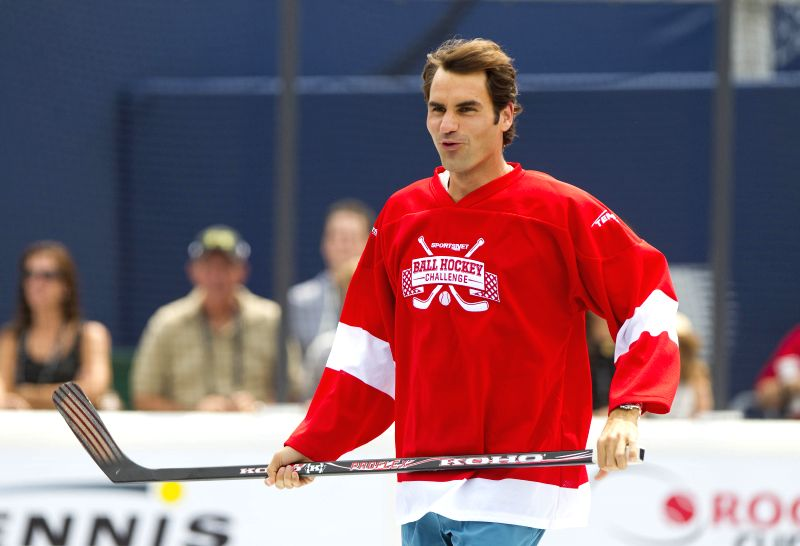 Roger Federer of Switzerland runs during the Ball Hockey Challenge game at the 2014 Rogers Cup in Toronto, Canada, Aug. 3, 2014.