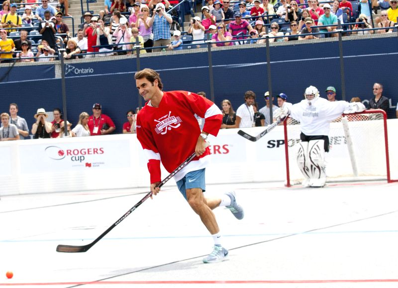 Roger Federer of Switzerland drives the ball before the Ball Hockey Challenge game at the 2014 Rogers Cup in Toronto, Canada, Aug. 3, 2014.