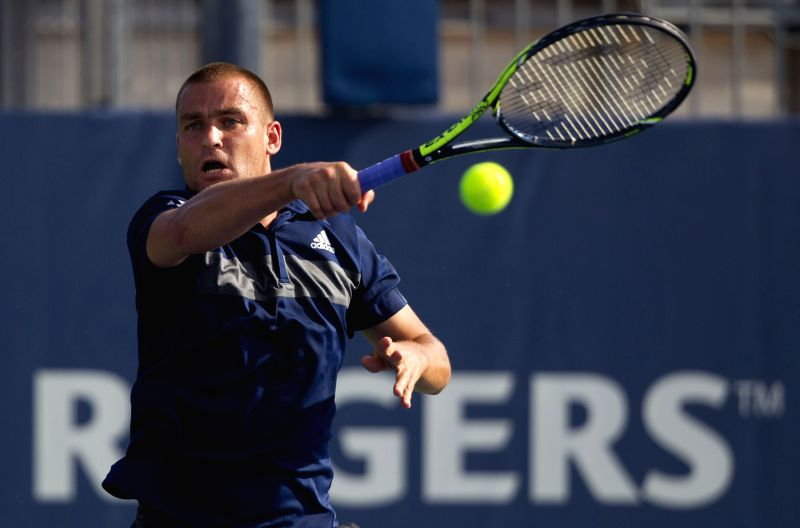 Mikhail Youzhny of Russia returns the ball during the first round of men's singles against Fabio Fognini of Italy at the 2014 Rogers Cup in Toronto, Canada, Aug. 5, ..