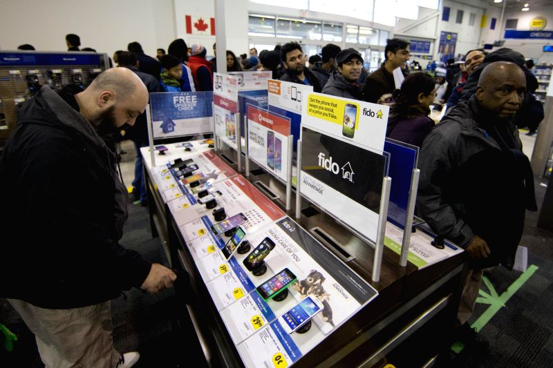 People buy mobile phones at the Best Buy store on the Boxing Day in Toronto, Canada, Dec. 26, 2014. Boxing Day sales has become a tradition in Canada. During the ..