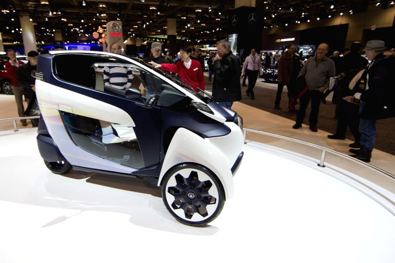 Visitors watch a three-wheeler Toyota i-Road electric concept car during the 2015 Canadian International Auto Show at the Metro Toronto Convention Centre in ...
