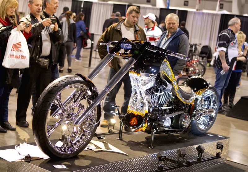 Visitors watch a motorcycle during the 39th North American International Motorcycle Supershow in Toronto, Canada, Jan. 3, 2015. As the largest consumer motorcycle ...