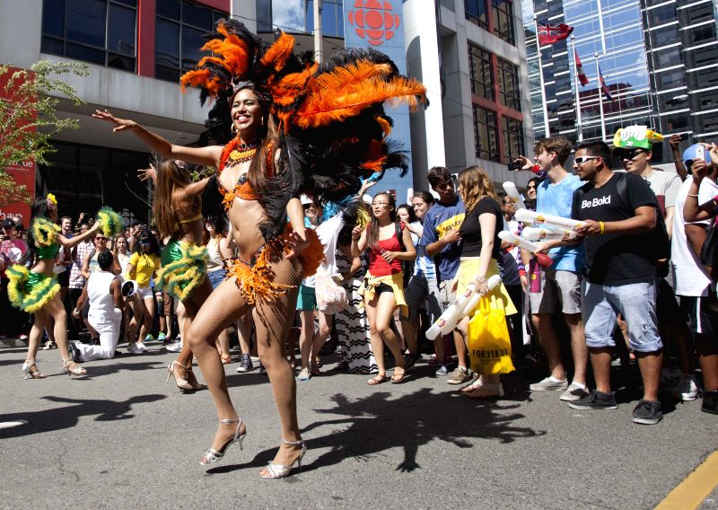 Dancers perform during the half-time break as fans watch the 2014 FIFA World Cup final between Germany and Argentina on the street in Toronto, Canada, July 13, ...