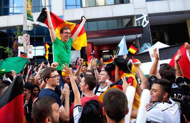 German fans celebrate victory while watching the 2014 FIFA World Cup final between Germany and Argentina on the street in Toronto, Canada, July 13, 2014. Germany ...