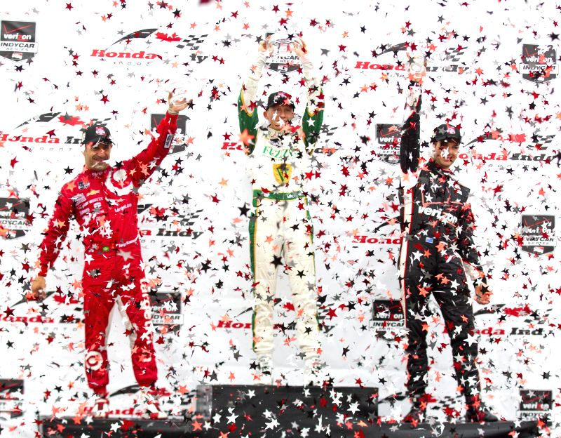 Ed Carpenter Racing's British driver Mike Conway (C), Target Chip Ganassi Racing's Tony Kanaan (L) and Team Penske's Will Power hold up their trophies to celebrate .