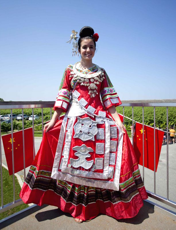 """A girl poses for photos wearing Miao ethnic group traditional clothes during the """"Colorful Guizhou Exhibition"""" in the Town of Niagara-on-the-Lake, ..."""