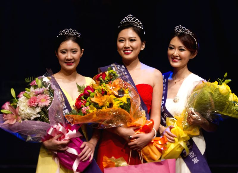 Winner Yvonne Liu (C), runner-up Xinyu Han (R) and second runner-up Sara Du pose for photos during the award ceremony of the Miss Chinese Cosmos Pageant 2014 ...