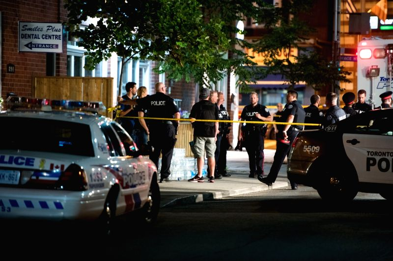 TORONTO, July 23, 2018 - Police officers gather at the crime scene in Toronto, Canada, on July 23, 2018. A man shot 14 people, killing one and injuring 13 others in Toronto's east-end neighborhood ...