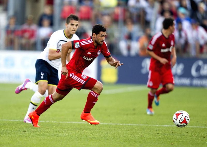 Gilberto (2nd L) of Toronto FC breaks through as Erik Lamela(L) of Tottenham Hotspur defends during their friendly match in Toronto, Canada, July 23, 2014. Tottenham