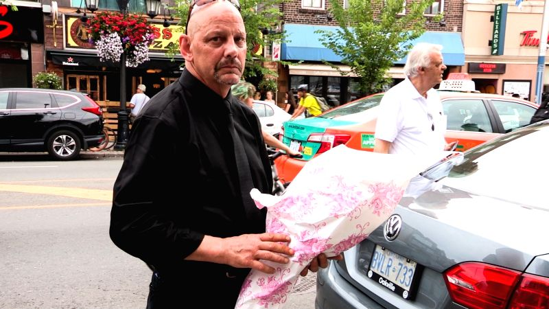 TORONTO, July 24, 2018 - A survivor goes back to the scene site with a bunch of flowers in Toronto, Canada, July 23, 2018. An 18-year-old female university student and a 10-year-old girl were killed, ...