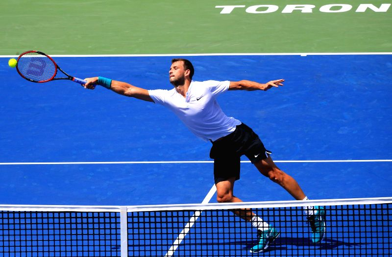 TORONTO, July 26, 2016 - Grigor Dimitrov of Bulgaria returns the ball against Yuichi Sugita of Japan during their first round of men's singles match at the 2016 Rogers Cup in Toronto, Canada, July ...