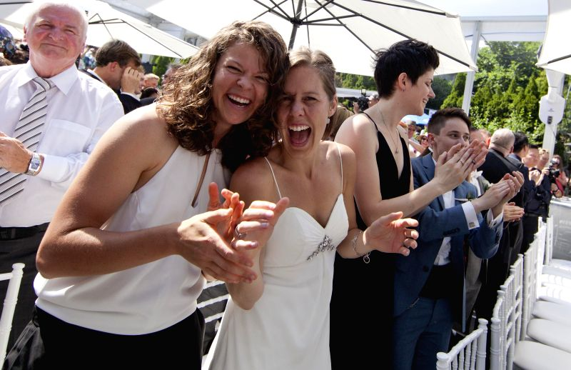 Couples celebrate during a LGBTQ mass wedding at Casa Loma in Toronto, Canada, June 26, 2014. A total of 110 LGBTQ  couples from around the world were married in ...