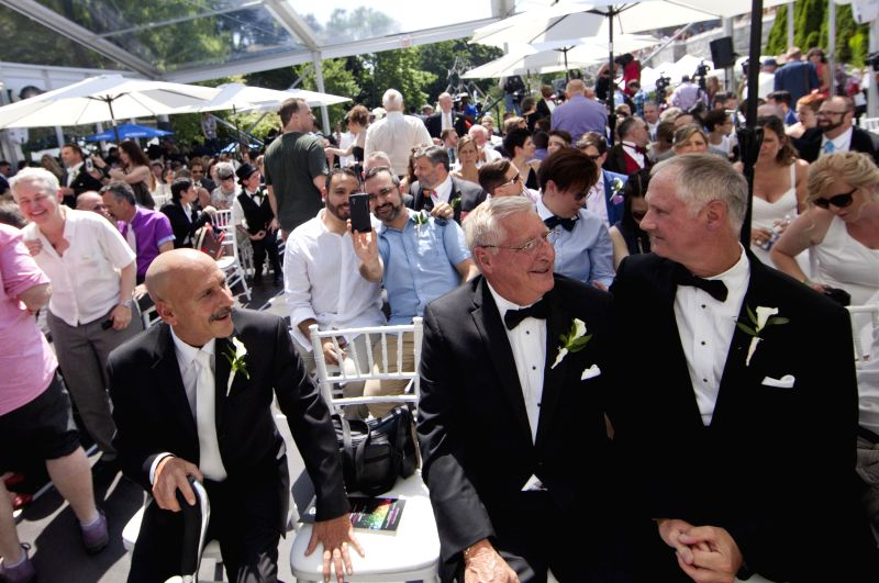 Couples take part in a LGBTQ mass wedding at Casa Loma in Toronto, Canada, June 26, 2014. A total of 110 LGBTQ  couples from around the world were married in ...