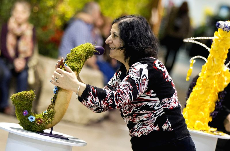 A woman poses with an exhibit as visiting the 2015 Canada Blooms in Toronto, Canada, March 13, 2015. As Canada's largest flower and garden festival, the 10-day ...