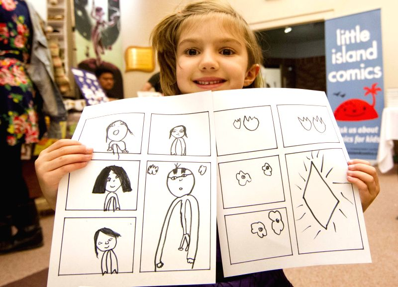 A girl shows the comics drew by herself at comics class during the 2014 Toronto Comic Arts Festival in Toronto, Canada, May 10, 2014. Focusing on readings, ...