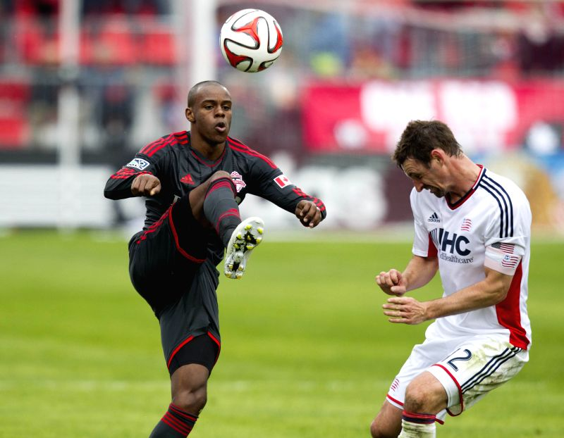 Jackson Goncalves (L) of Toronto FC kicks the ball during the 2014 Major League Soccer (MLS) match against New England Revolution in Toronto, Canada, May 3, 2014. ...