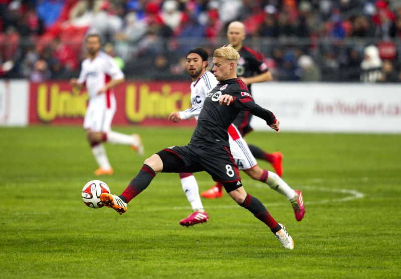 Kyle Bekker(Front) of Toronto FC kicks the ball during the 2014 Major League Soccer (MLS) match against New England Revolution in Toronto, Canada, May 3, 2014. ...
