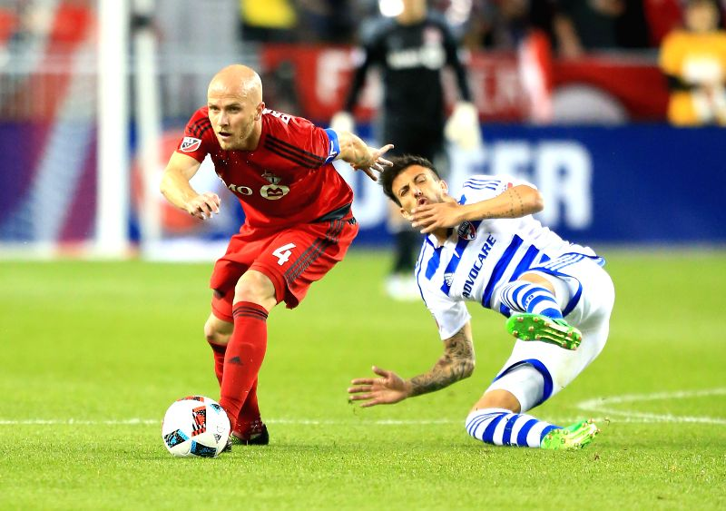 TORONTO, May 8, 2016 - Michael Bradley (L) of Toronto FC vies with Maximiliano Urruti of FC Dallas during the 2016 Major League Soccer (MLS) match in Toronto, Canada, May 7, 2016. Toronto FC won 1-0.