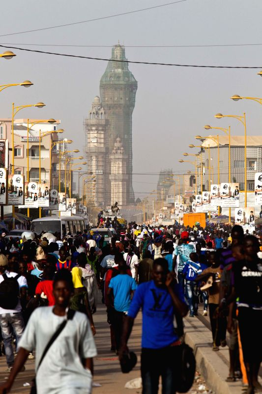 Pilgrims walk on the main street near the Grand Mosque of Touba, Senegal's holy city, Dec. 10, 2014. Senegalese will celebrate the festival of Grand Magal on Thursday, an annual pilgrimage ...