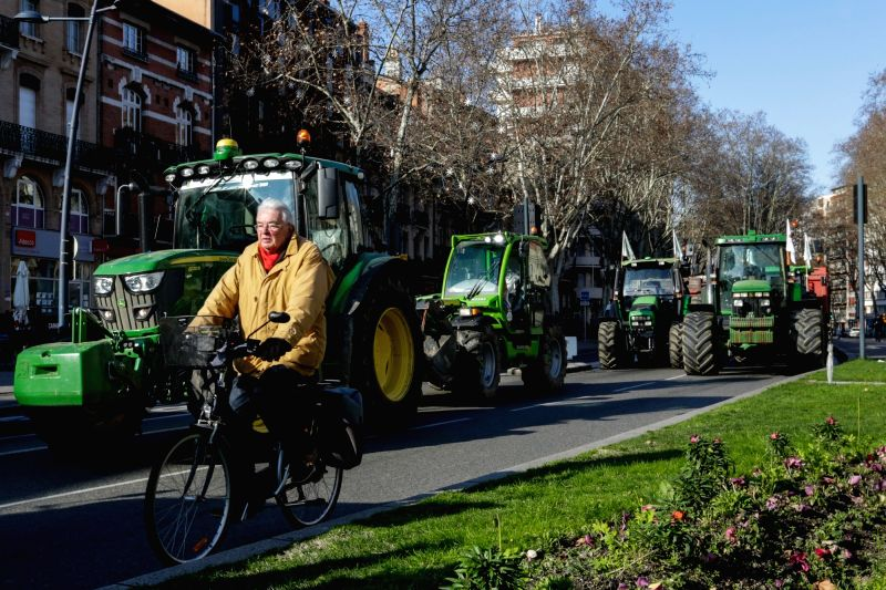 TOULOUSE, Feb. 1, 2018 - A cyclist passes by the tractors in demonstration in Toulouse, France, Jan. 31, 2018. Farmers set up a filter dam on Wednesday to slow down traffic to protest against the ...