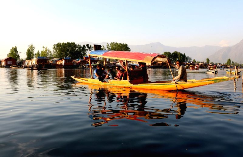 Tourists enjoy a Shikara ride on Dal Lake in Srinagar, on May 7, 2016.