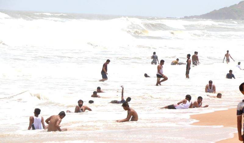 Tourists enjoy themselves at Goa's Calangute Beach despite warnings from lifeguards, on June 13, 2018.