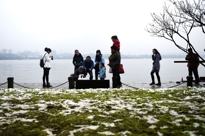 Tourists take photo of snowmen on the Bai Causewayat the West Lake in Hangzhou, capital of east China's Zhejiang Province, Dec. 6, 2015. (Xinhua/Huang Zongzhi) ...