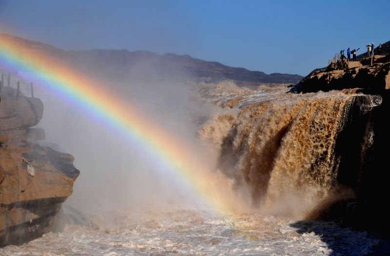 Tourists take pictures of a rainbow over the Hukou Waterfall along the Yellow River in Jixian County, north China's Shanxi Province, Oct. 27, 2015. (Xinhua/Lyu ...