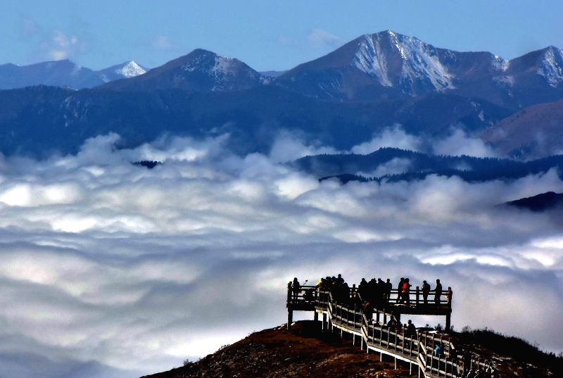 Tourists visit the Huanglong scenic spot, a World Heritage site famous for its colorful pools and snowy mountains, in southwest China's Sichuan Province, Oct. 25, 2015. ...